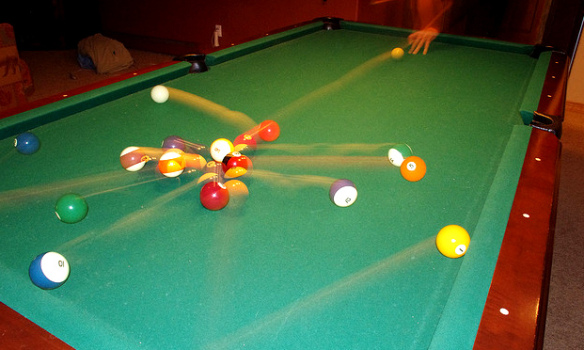 Photo of balls scattering on a pool table.
